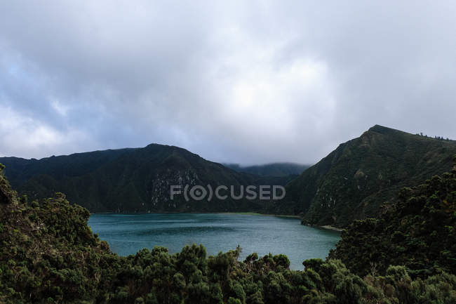 Amazing landscape with calm lake and mountains covered with green vegetation at cloudy day — Stock Photo