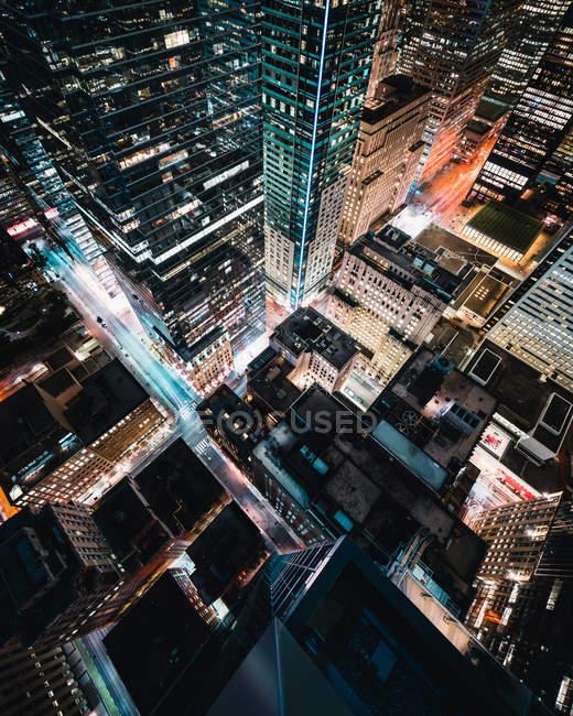Vista aérea de la ciudad con edificios de gran altura por la noche - foto de stock