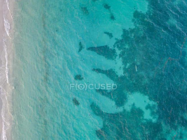 Vista aerea di acqua chiara blu e verde oceano a fianco di una spiaggia. — Foto stock