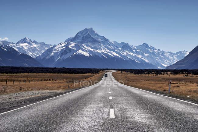 Бетонная дорога к красивым заснеженным горам в солнечный день — стоковое фото