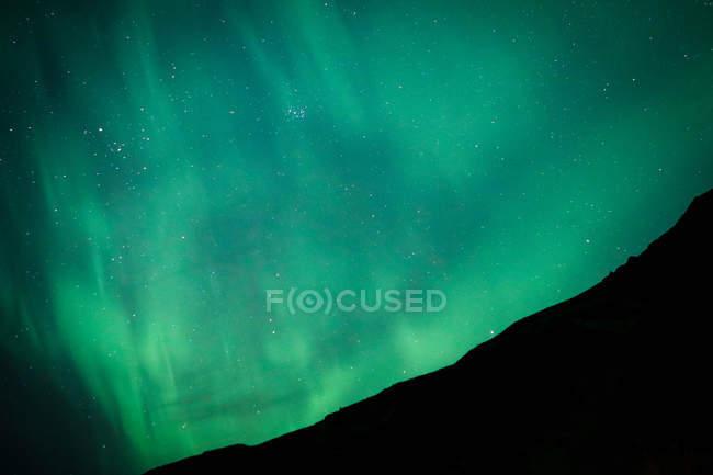 Fenômeno verde da Aurora no céu acima da montanha escura — Fotografia de Stock