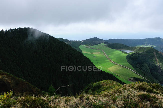 Aerial view of beautiful green field and mountains covered with lush vegetation — Stock Photo