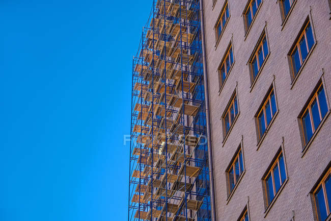 Low angle view of grey high rise building against clear blue sky — стокове фото