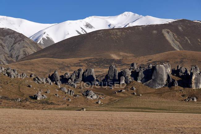 Красивые горы с сухой местности и снег на вершинах в солнечный день — стоковое фото