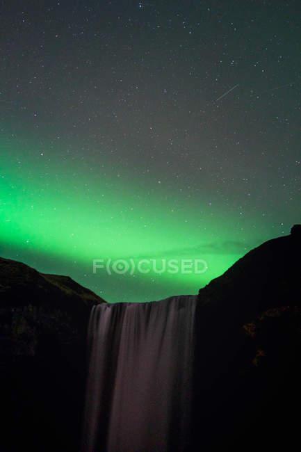 Erstaunliche natürliche Ansicht der Aurora borealis über Wasserfall — Stockfoto