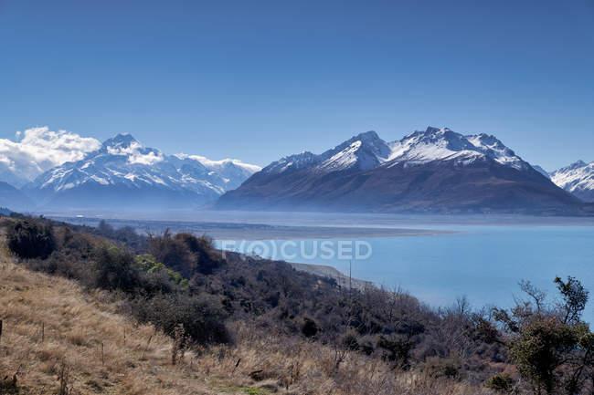 Удивительный пейзаж с травой и кустарниками на берегу, спокойный водоем и скалистые горы со снегом на вершинах в солнечный день — стоковое фото