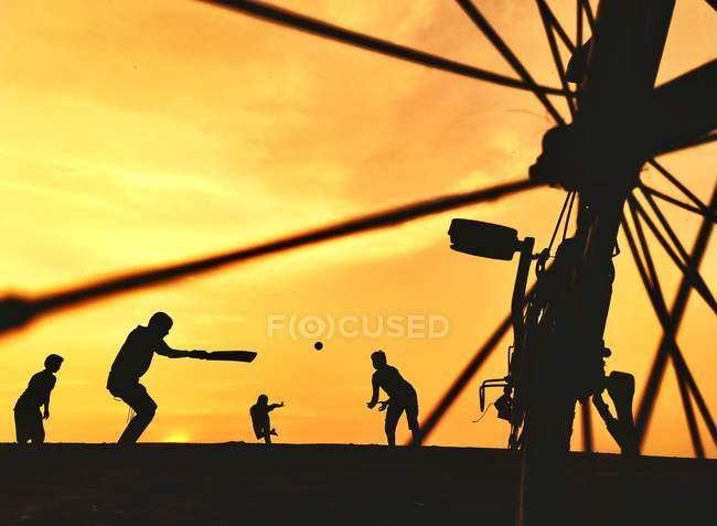 Silhouettes of people playing cricket against beautiful sunset sky and bicycle on foreground, selective focus — стокове фото