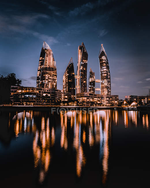 Low angle view of night skyline of skyscrapers in Dubai reflected in water - foto de stock