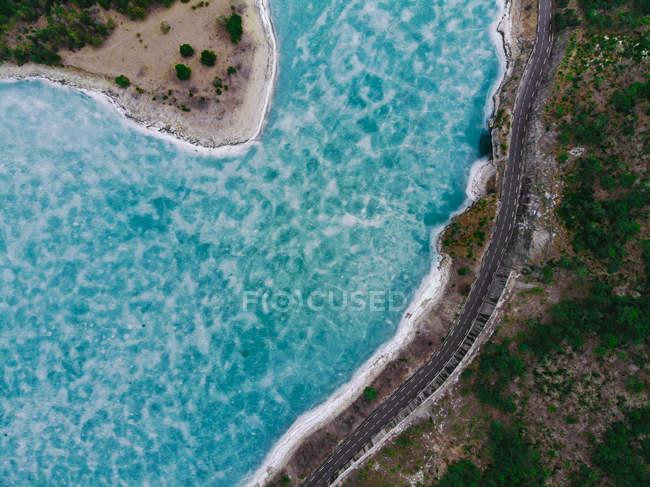 Vista aerea della strada costiera e calma acqua blu durante il giorno — Foto stock