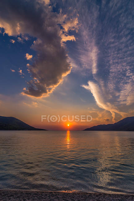 Blue sea viewing mountains under orange and blue sky — Stock Photo