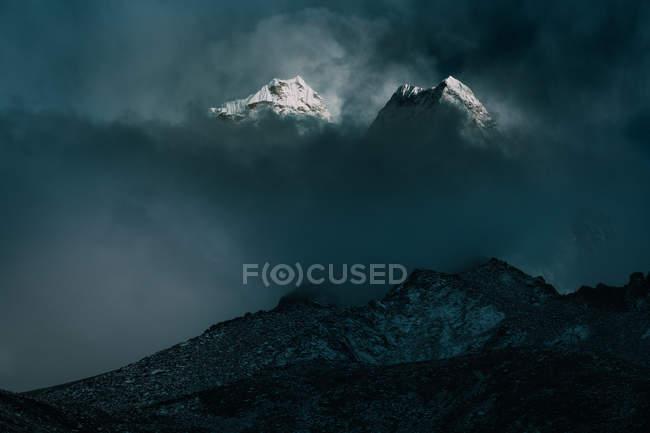 Vista ad angolo basso delle maestose montagne del ghiacciaio tra le nuvole — Foto stock