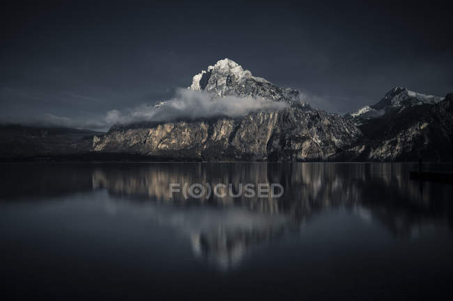 Amazing snow-covered gray mountains with fog reflected in calm lake — Stock Photo