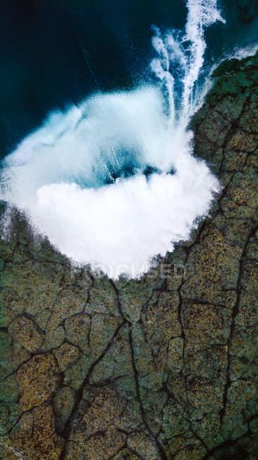 Aerial view of ocean wave crashing to rocky shore - foto de stock