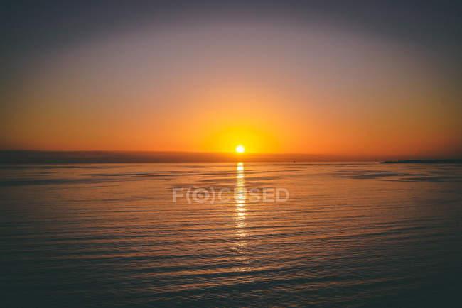 Corpo calmo bonito da água durante o por do sol cénico — Fotografia de Stock
