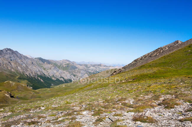 Beautiful rocky mountains with green grass under blue sky — Stock Photo