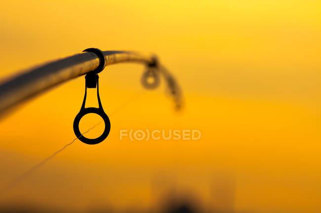 Fotografía de enfoque selectivo de la caña de pescar contra el cielo de puesta de sol naranja - foto de stock