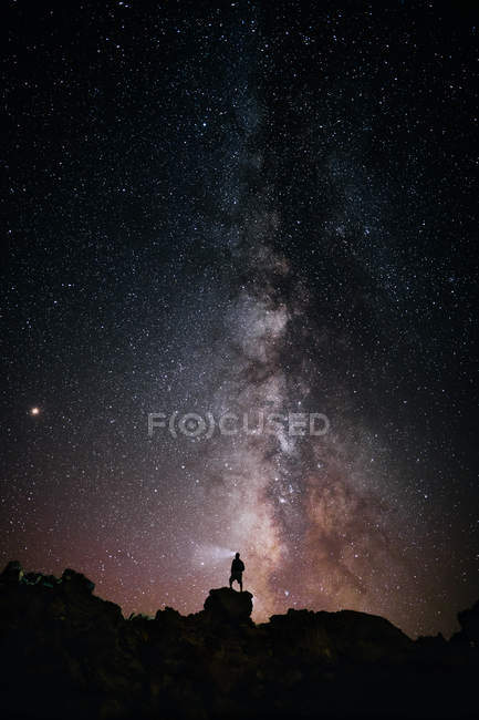 Silhouette of person with flashlight standing on rock against majestic starry night sky — стокове фото