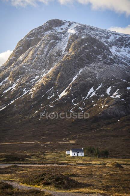 Kleine weiße Kirche in der Nähe majestätischen Berg mit Schnee auf dem Gipfel — Stockfoto