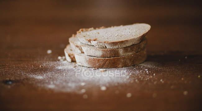 Vista de primer plano de tres rebanadas de pan y harina sobre mesa de madera - foto de stock