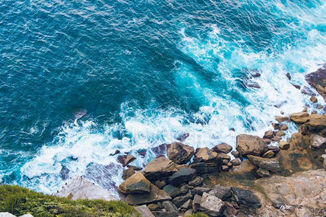 Высокий угол зрения красивых синих морских волн и скал на побережье — стоковое фото