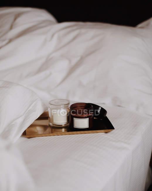 Duas velas da coluna na bandeja de madeira na cama com fundamento branco — Fotografia de Stock