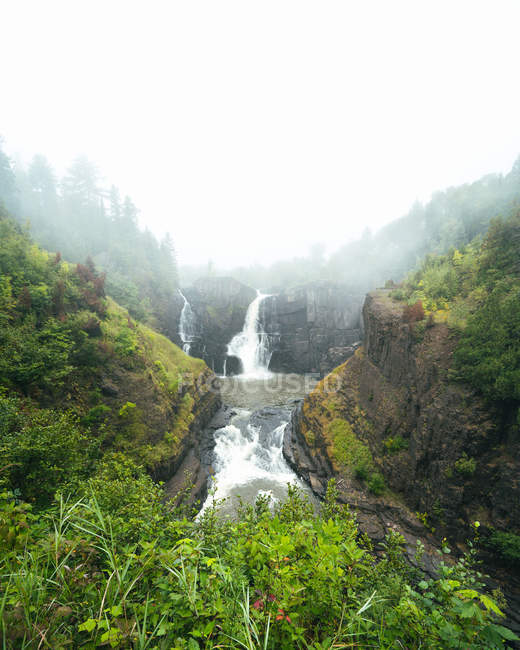 Erstaunliche Wasserfälle in der Nähe von malerischen Bergen mit grüner Vegetation und Felsen bedeckt — Stockfoto