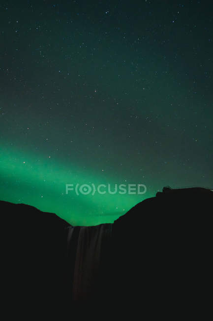 Majestic landscape with northern lights in sky over waterfall — Stock Photo