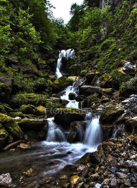 Amazing waterfalls near scenic mountains covered with green vegetation and rocks — Stock Photo