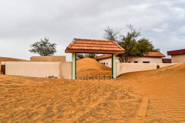 Casas e portas concretas brancas na areia no dia nebuloso — Fotografia de Stock