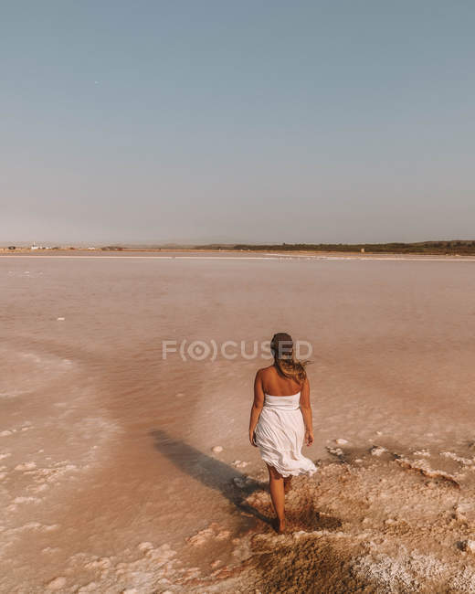 Back view of woman wearing white dress walking on sandy beach, high angle view — Stockfoto