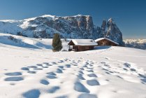 Traditional huts of the Dolomites after a winter snowfall overlook the scenery of the Group Sciliar, Siusi, Western Dolomites, Trentino-Alto Adige, Italy, Europe — Stock Photo