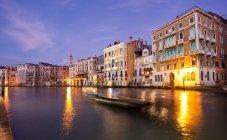 Una gondola solitaria che scivola lungo le acque del Canal Grande di notte, Venezia, Veneto, Italia, Europa — Foto stock