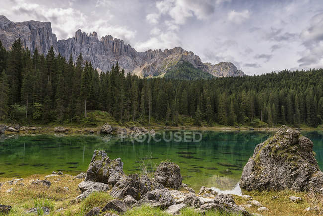 Lac de Karersee et le groupe de montagne de Latemar dans une journée nuageuse, Dolomites, Trentino-Alto Adige, Italie — Photo de stock