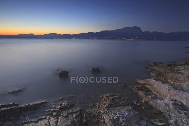 Twilight on Garda lake with Pizzoccolo peak in background, Sirens bay, Garda lake, Veneto, Italy — Stock Photo
