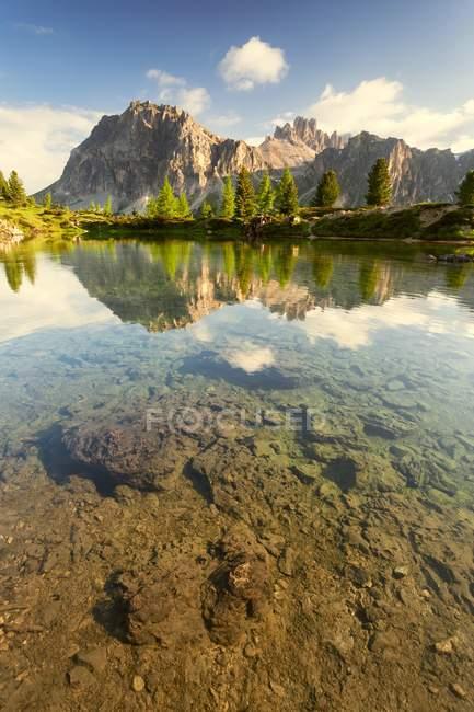 Невелике альпійське озеро Лілідес вранці на початку літа. Модрина і ялини з їх яскравими квітами виділяються на відміну від стін Lagazuoi ще частково в тіні. Доломіти, район Фальзаего, Венето, Італія — стокове фото
