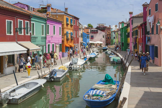 Many tourists walking on a Burano streets along the canal, passing trough the typical colorful houses, Burano, Venice, Veneto, Italy — Stock Photo