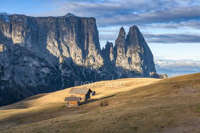 Traditional mountain huts on the Alpe di Siusi meadows, in the background the Sciliar, Alpe di Siusi, Dolomites, Trentino-Alto Adige, Italy — Stock Photo