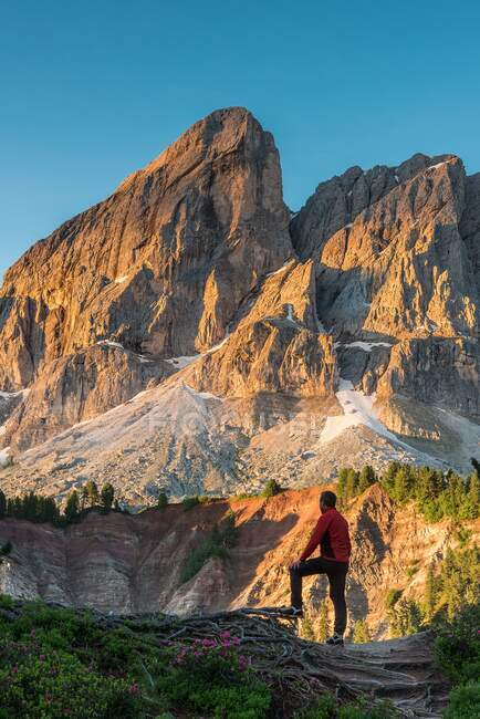 A hiker admires the sun rising at Sass de Putia/Peitlerkofel, Passo delle Erbe, Dolomites, Trentino-Alto Adige, Italy — Stock Photo