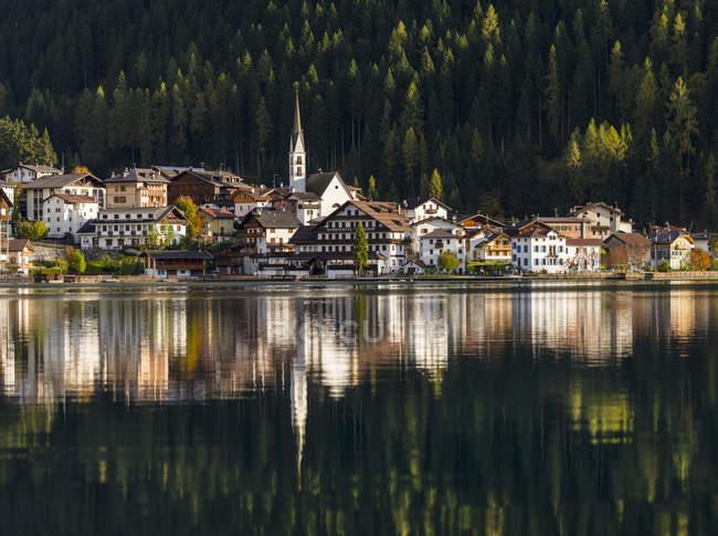 Village Alleghe en Lago di Alleghe al pie del monte Civetta, uno de los iconos de los Dolomitas del Véneto. Los Dolomitas del Véneto son parte del patrimonio mundial de la UNESCO. Europa, Europa Central, Italia, octubre - foto de stock