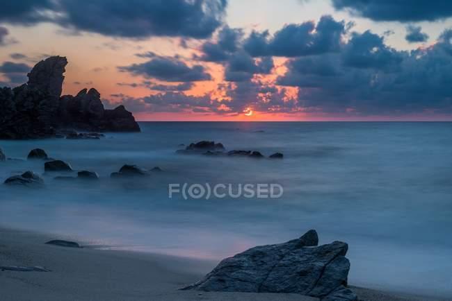 Tramonto sulla spiaggia di Capo Cozzo in Calabria con la Roccia del Leone, Zambrone, Calabria, Italia — Foto stock