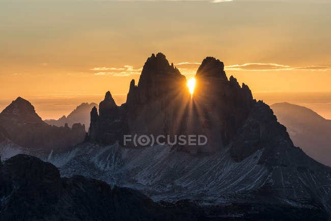 The sun rises exactly in between the crags of the Tre Cime di Lavaredo. This effect occurs only few days per year, exactly during winter solstice days, Picco di Vallandro, Prato Piazza, Dolomites, Trentino-Alto Adige, Italy — Stock Photo
