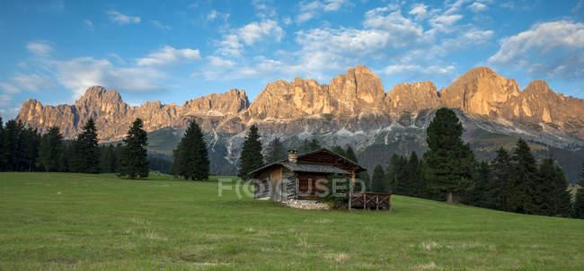Cabana da montanha nos pastos de Colbleggio, no fundo os picos do grupo de Catinaccio/Rosengarten, Carezza, Dolomites, Trentino-Alto Adige, Italy — Fotografia de Stock