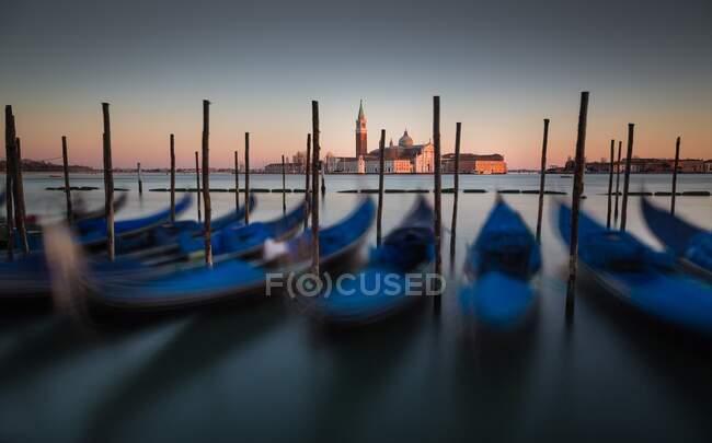 Vista da catedral de San Giorgio durante um pôr do sol de inverno tranquilo, com gôndolas em primeiro plano, Veneza, Veneto, Itália — Fotografia de Stock