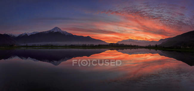 Panoramic view of Pian di Spagna flooded with snowy peaks reflected in the water at sunset Valtellina Lombardy, Italy, Europe — Stock Photo