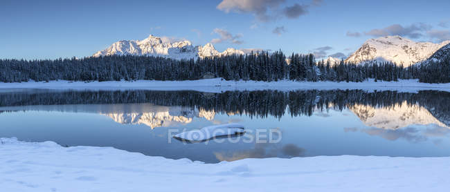 Wooden cabin surrounded by snowy peaks and woods reflected in Pal Lake at dawn, Malenco Valley, Valtellina, Lombardy, Italy, Europe — Stock Photo