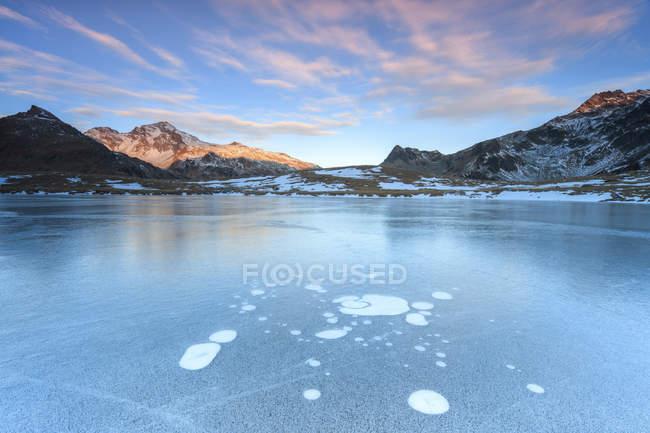 Льодові бульбашки на замерзлотій поверхні озера Andossi на світанку Vallesplug, Вальтелліна, Ломбардія, Італія, Європа — стокове фото