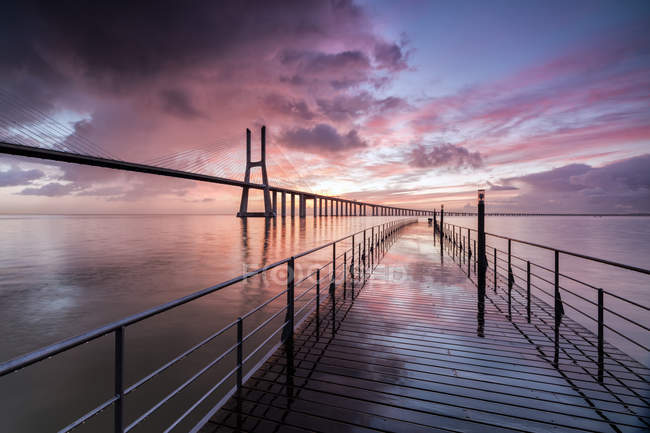 Sunrise colors the clouds reflected in Tagus River and frame the Vasco da Gama bridge in Lisbon, Estremadura, Portugal, Europe — Stock Photo