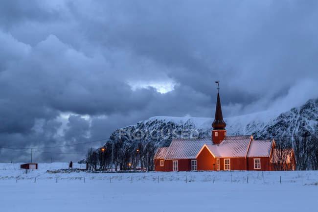 Luci sulla chiesa al crepuscolo con le cime innevate sullo sfondo Flakstad, Isole Lofoten, Norvegia, Europa — Foto stock