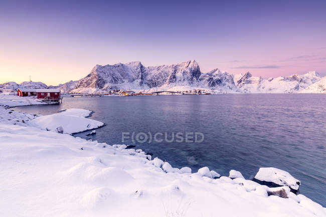Los colores del amanecer enmarcan las casas de pescadores rodeadas de mar congelado Reine Bay Nordland, Islas Lofoten, Noruega, Europa - foto de stock