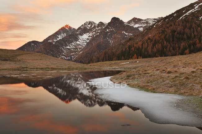 Il gruppo Tre Signori si riflette in un piccolo lago nella pianura di Avaro, nella valle Brembana, Lombardia, Italia — Foto stock